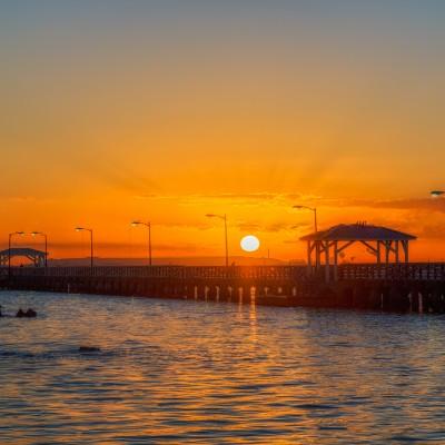 Sun fully risen over Ballast Point Park Pier, Tampa, Florida